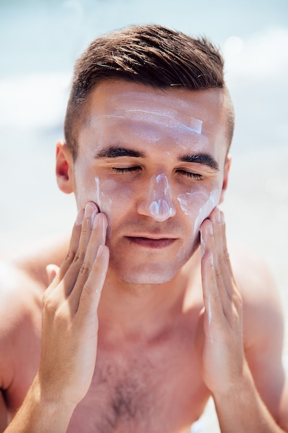 Young man putting tanning cream on his face, sunbathing on the beach. healthcare. Free Photo