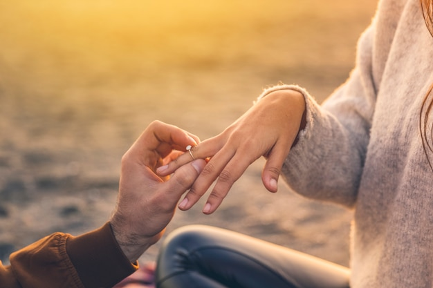 Young man putting wedding ring on woman finger Free Photo