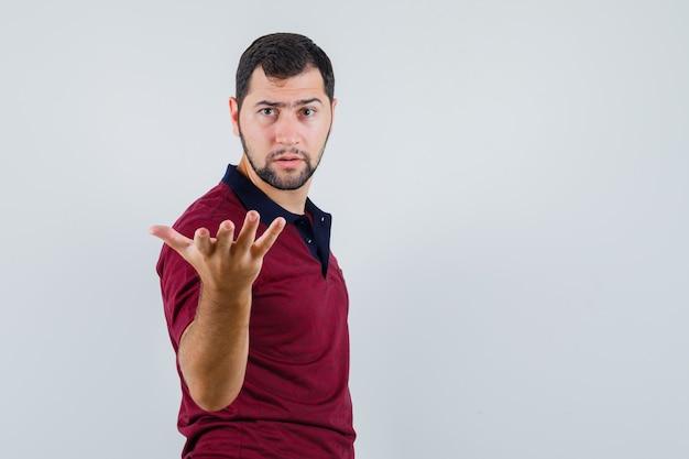 Giovane che alza la mano nel gesto interrogativo in maglietta e che sembra serio. vista frontale. Foto Gratuite