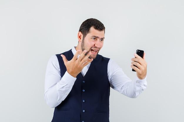 Молодой человек поднимает руку во время видеочата в рубашке и жилете и выглядит агрессивно Бесплатные Фотографии