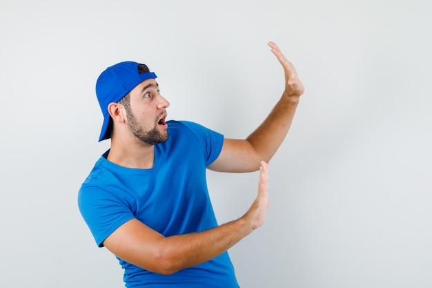 青いtシャツとキャップで予防的に手を上げて怖がっている若い男 無料写真