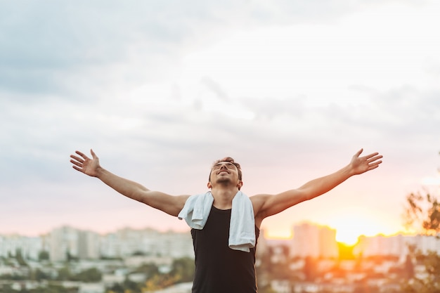 Young man raising hands over sunset sky after training Free Photo