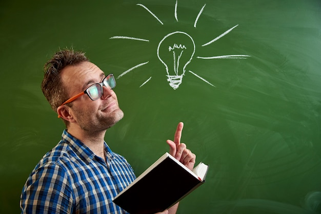 A young man reading a book, an idea comes to mind with a blackboard with a chalked light bulb. Premium Photo