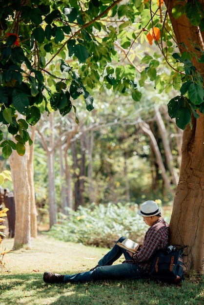 Young man reading book at lawn in summer Free Photo