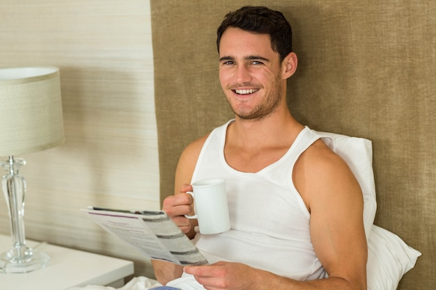 Young man reading newspaper while holding a cup of tea in bedroom Premium Photo