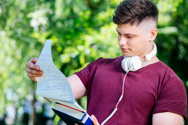 Young man reading notebook in park Free Photo