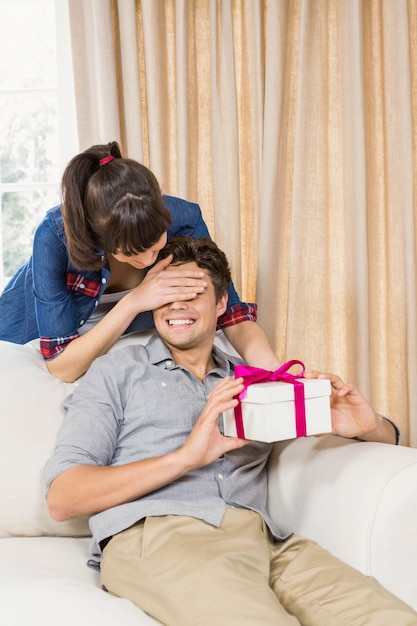 Young man receiving a surprise gift box from young woman at home Premium Photo