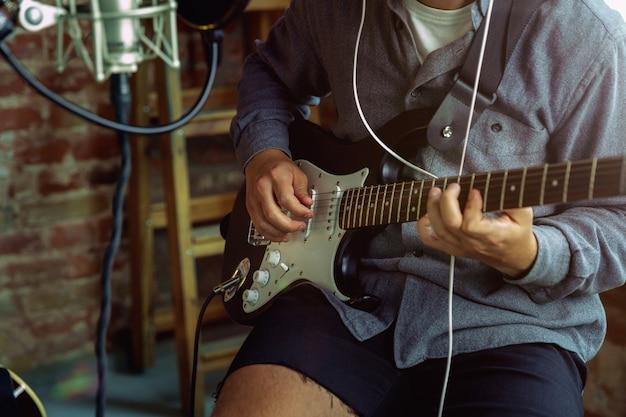 Giovane che registra musica, suonare la chitarra e cantare a casa Foto Gratuite