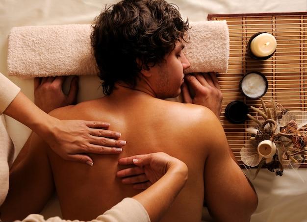 Il giovane uomo in relax, ricreazione, sano massaggio in un salone di bellezza. veduta dall'alto. luce chiave bassa Foto Gratuite