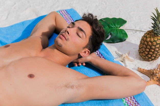 Young man relaxing on beach Free Photo