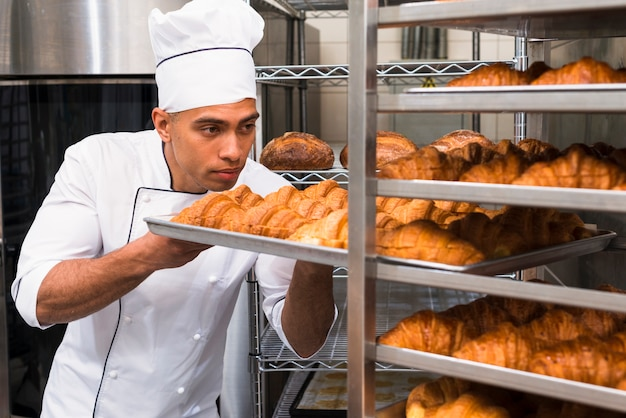 Young man removing the baking croissant tray from the shelf Free Photo