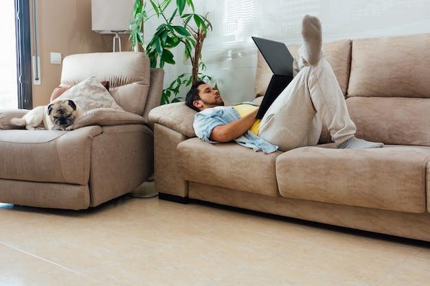 自宅のソファで休んでいて、彼のそばに犬と一緒にラップトップを使用している若い男 無料写真