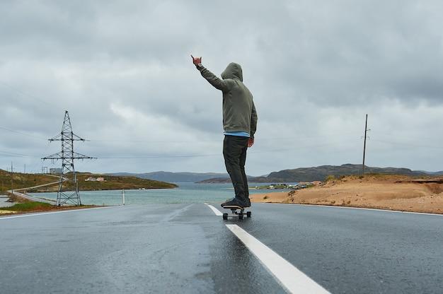 夏には、背面の空の曲がりくねった山道でロングボードに乗って若い男。 Premium写真
