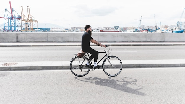 Young man riding the bicycle on road near the harbor Free Photo