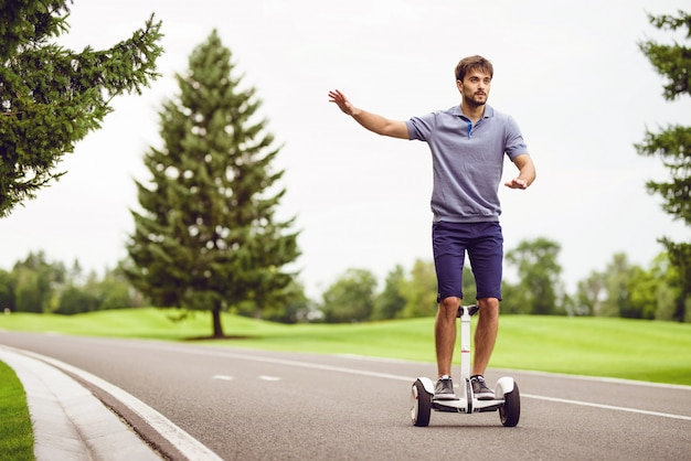 Young man riding a gyroboard along the way. Premium Photo