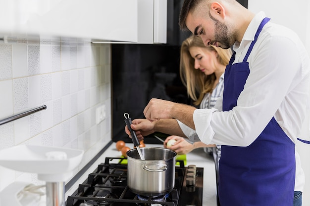 Young man salting water in pot near woman Free Photo
