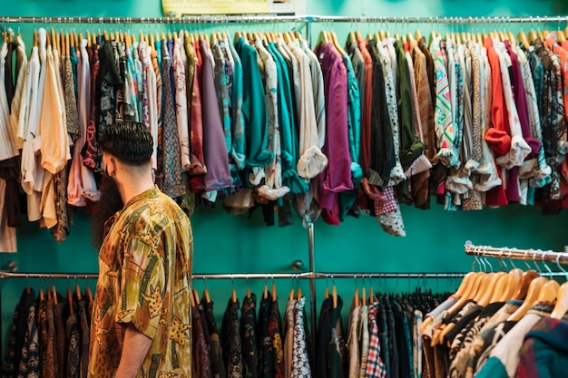 Young man in shirt choosing clothes in mall or clothing store Free Photo