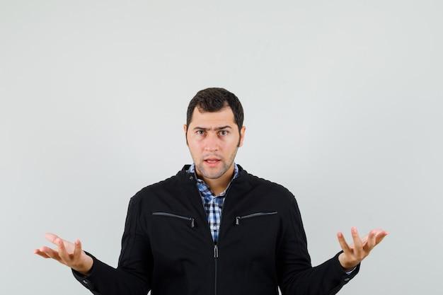 Giovane uomo in camicia, giacca tenendo le mani nel gesto interrogativo e guardando serio Foto Gratuite