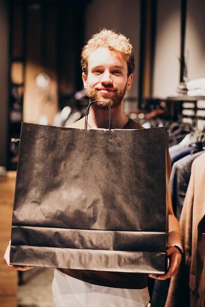 Young man shopping at menswear shop Free Photo