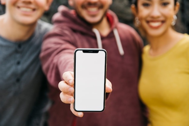 Young man showing blank space of smartphone while standing near multiracial friends Free Photo
