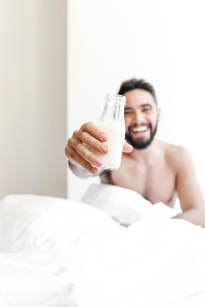 Young man showing bottle of milk Free Photo