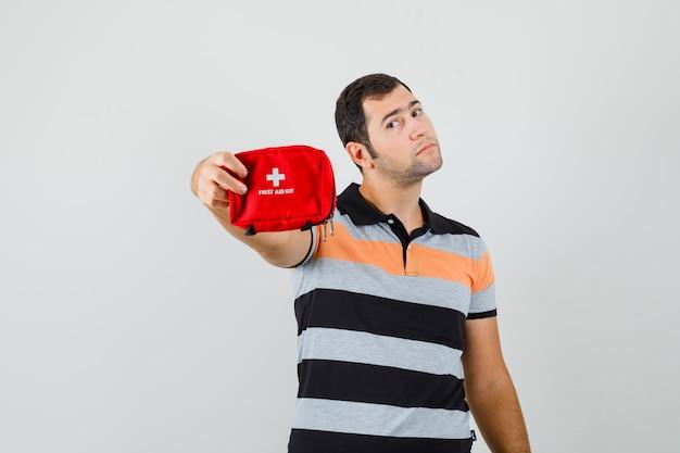 Молодой человек показывает аптечку в футболке и выглядит уверенно. передний план. Бесплатные Фотографии