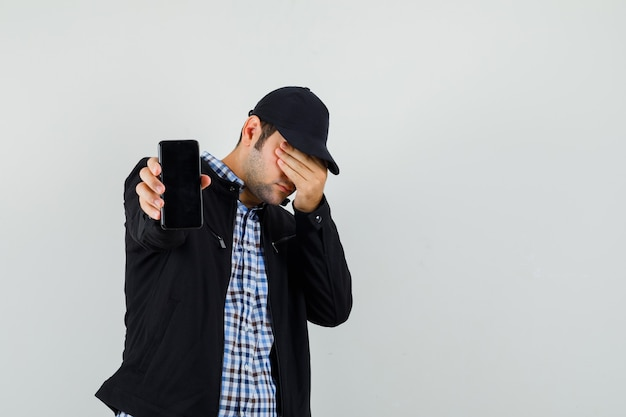 Молодой человек показывает мобильный телефон, держа руку на глазах в рубашке, куртке, кепке, вид спереди. Бесплатные Фотографии