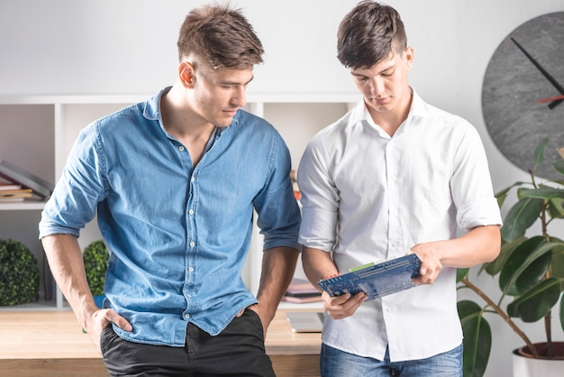 Young man showing motherboard to his friend Free Photo