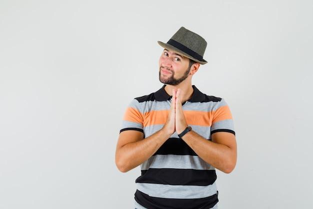 Tシャツ、帽子、感謝の気持ちでナマステのジェスチャーを示す若い男 無料写真