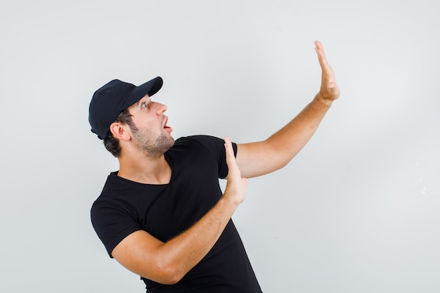 Young man showing refusal gesture in black t-shirt Free Photo
