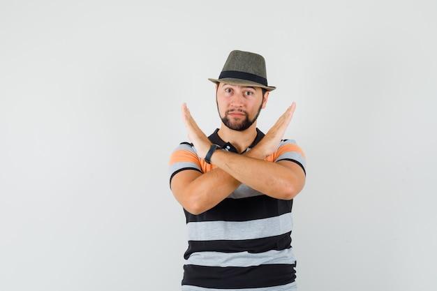 Молодой человек показывает жест отказа в футболке, шляпе и выглядит решительным. Бесплатные Фотографии