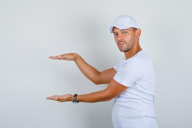 Молодой человек показывает знак размера руками в белой футболке, кепке, вид спереди. Бесплатные Фотографии