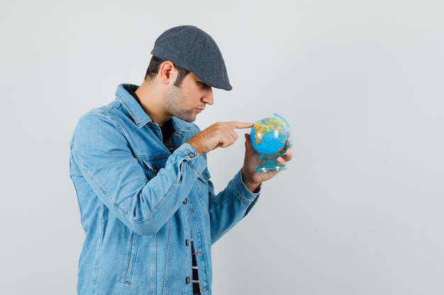재킷, 모자에 미니 글로브 어딘가에 표시 하 고 집중 찾고 젊은 남자. 전면보기. 무료 사진