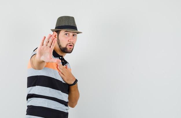 Молодой человек показывает жест стоп, держит руку на груди в футболке, шляпе и выглядит взволнованным, Бесплатные Фотографии