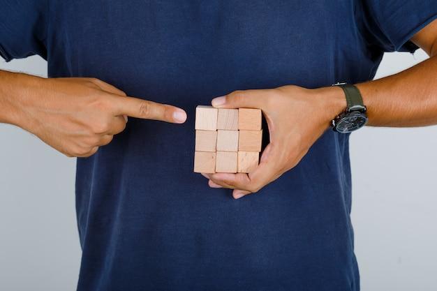 Giovane che mostra i blocchi di legno nella vista frontale della maglietta blu scuro. Foto Gratuite