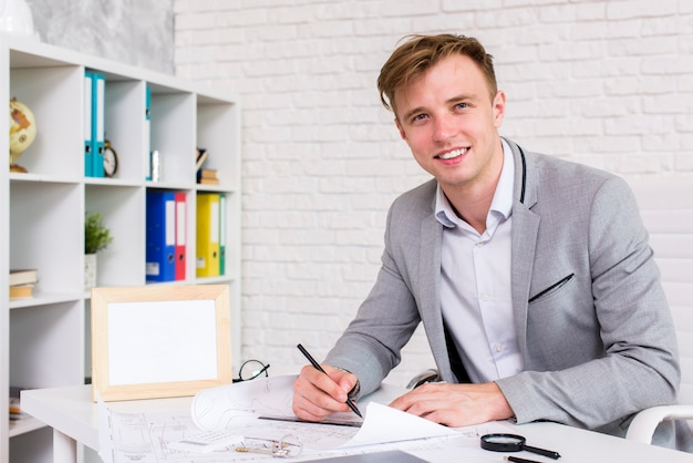 Young man signing a document while looking at the camera Free Photo