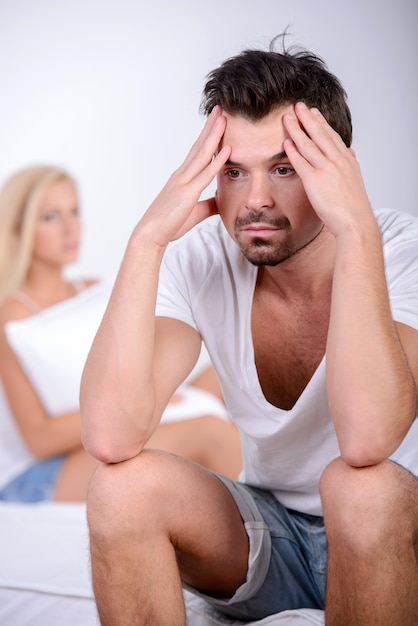 Young man sitting on the bed, against his angry wife. Premium Photo