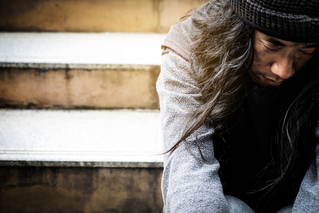 Young man sitting begging in the capita Premium Photo