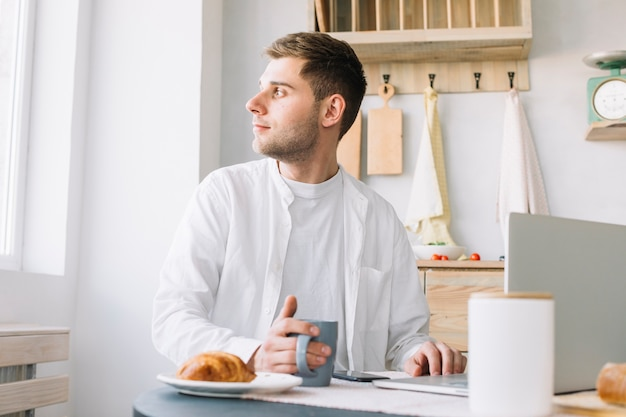 Young man sitting in front of table with laptop and food looking out through window Free Photo