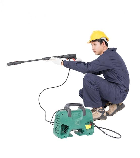 Young man sitting and holding high pressure water gun Premium Photo