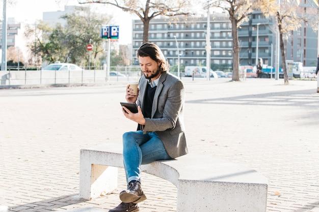 Молодой человек сидит в городском парке и смотрит на мобильный телефон с чашкой кофе на вынос Бесплатные Фотографии