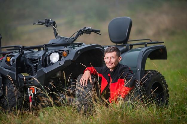 Young man sitting near four-wheeler atv Premium Photo