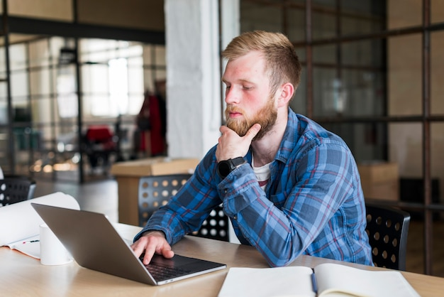 Young man sitting in office using laptop Free Photo