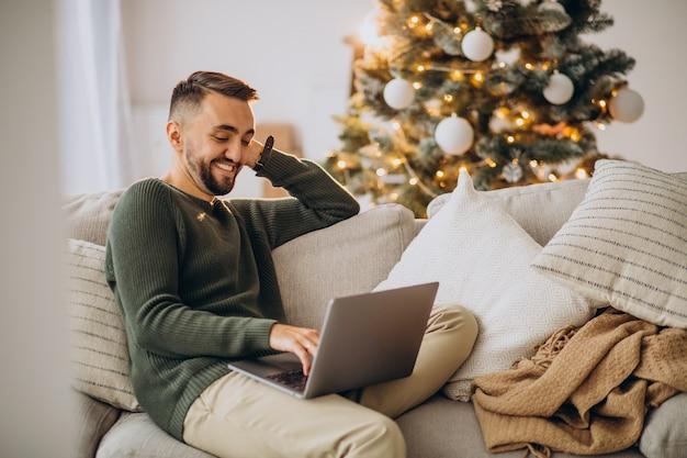 Молодой человек сидит на диване и использует ноутбук на рождество Бесплатные Фотографии