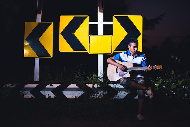 Young man sitting and playing guitar on road side with road sign background, journey of musician concept Premium Photo