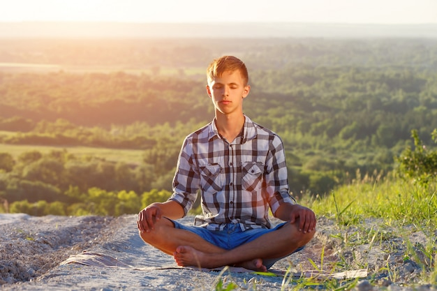 Young man sitting on the road in lotus position on a sunny day Premium Photo