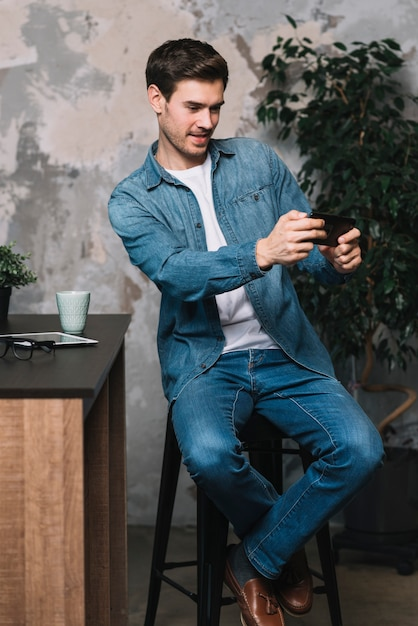 Young man sitting on stool taking selfie through cellphone Free Photo