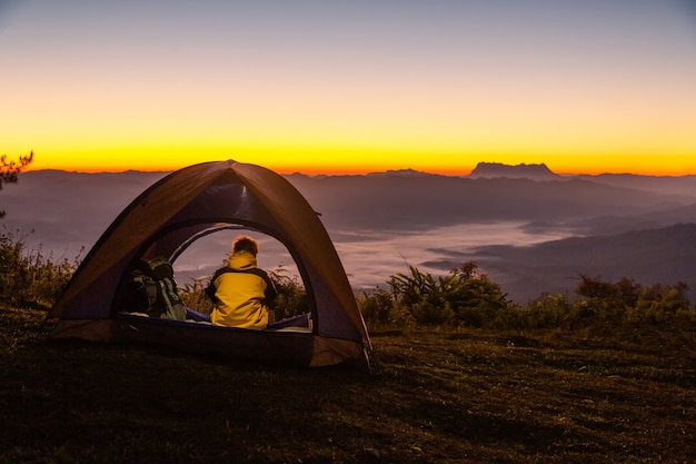 A young man sitting in the tent with looking at the mountain landscape in winter Free Photo