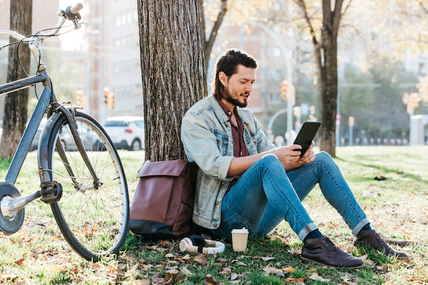 Young man sitting under the tree using mobile phone in the park with takeaway coffee paper cup Free Photo