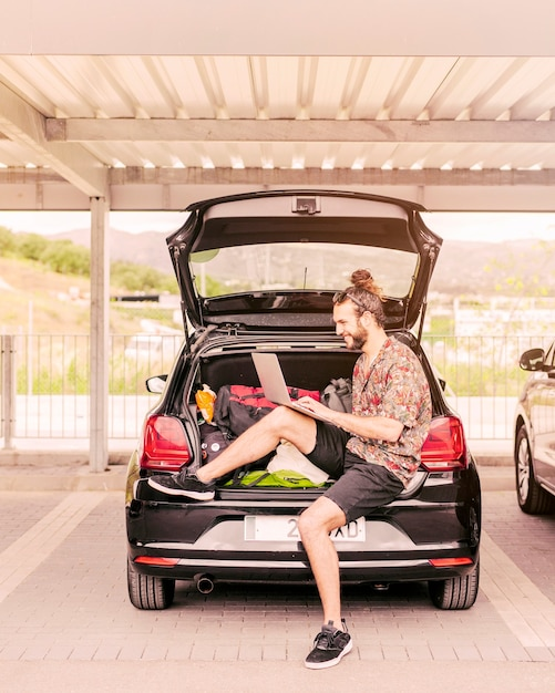 Young man sitting in trunk with laptop Free Photo